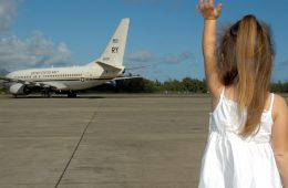 une petite fille saluant un avion sur une piste