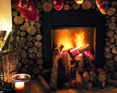 Cheminée en feu avec des chaussettes de Noël pendues et des bougies à côté