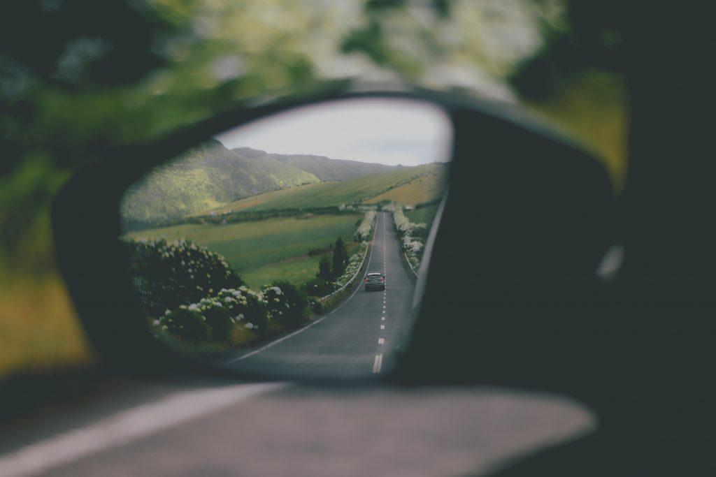 une route boisée dans le reflet d'un rétroviseur de voiture