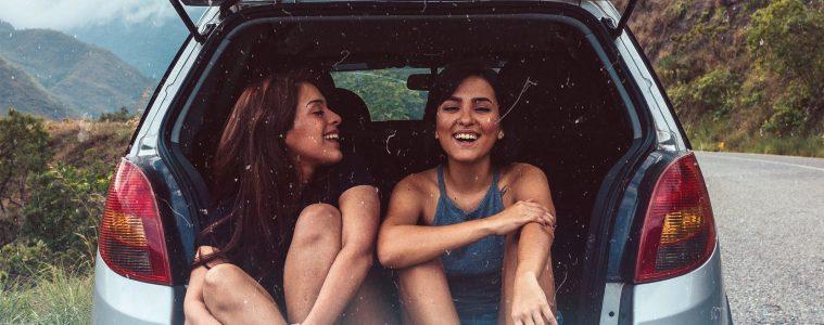 Deux femmes assises dans le coffre d'une petite voiture
