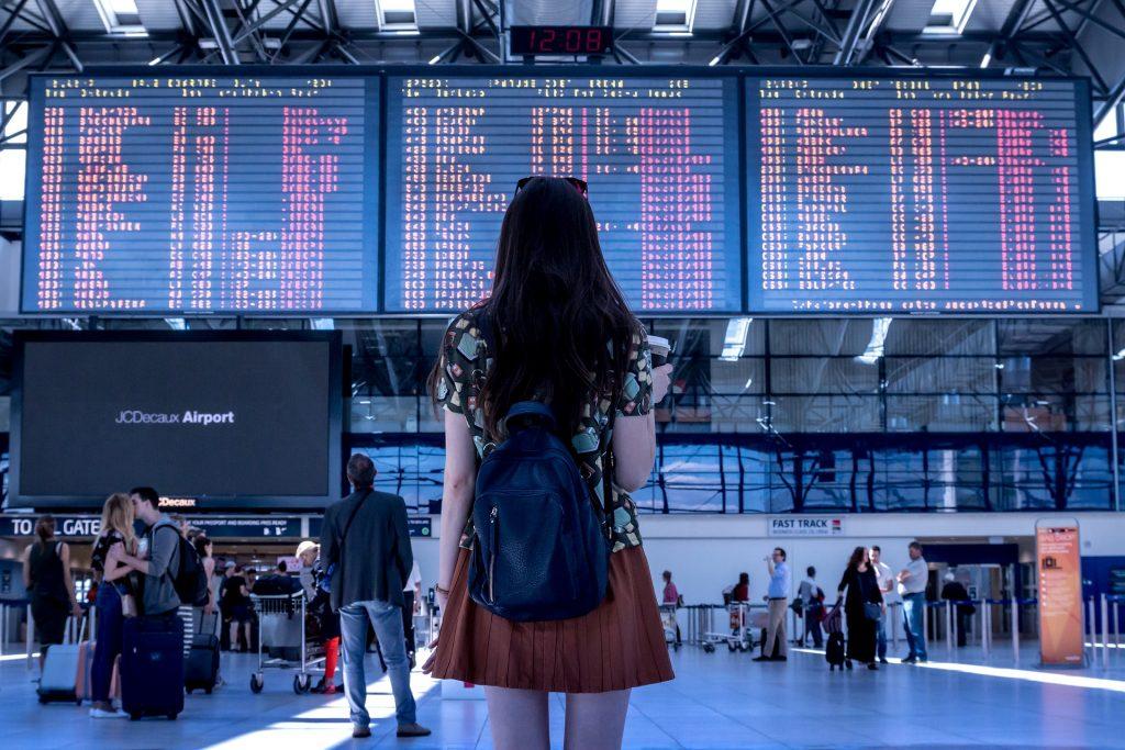 Femme de dos regardant un panneau de départs d'avions