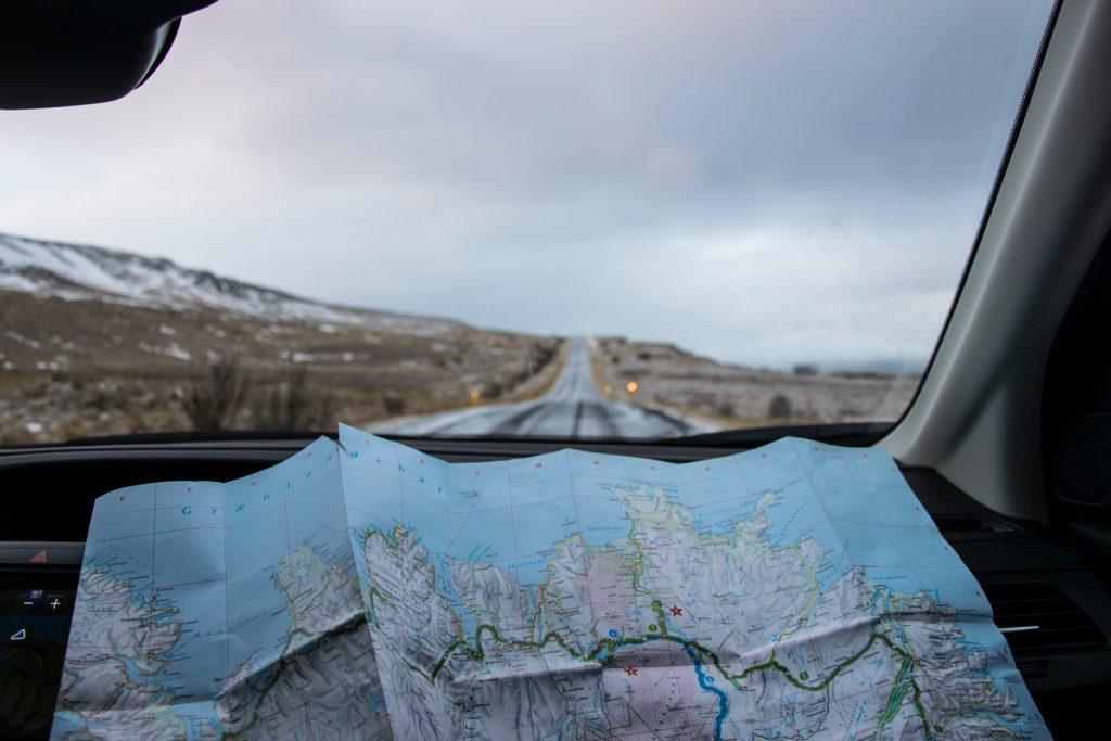 Une carte dépliée à l'avant d'une voiture sur une route déserte