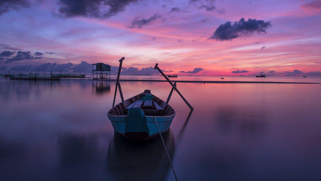 vacances dernière minute, bateau sur l'eau avec coucher de soleil